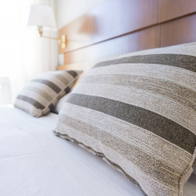 hotel bed with striped pillows and white sheets